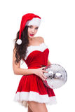 Sexy young woman in Christmas wear and hat holding disco ball. isolated on white background. Royalty Free Stock Images