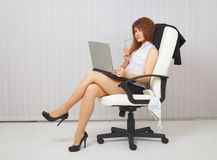young woman with computer in office chair Stock Photos
