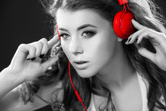 Sexy young woman dancing listening to music in headphones. Woman dancing listening to music in headphones from smart phone or mp3 player. Sexy happy young woman Stock Images