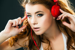 Sexy young woman dancing listening to music in headphones. Woman dancing listening to music in headphones from smart phone or mp3 player. Sexy happy young woman Royalty Free Stock Images