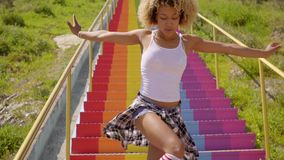 young woman dancing on rainbow colored steps stock video footage