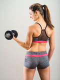 Sexy young woman doing dumbbell curl. Photo of an attractive woman doing a dumbbell curl while standing Royalty Free Stock Image