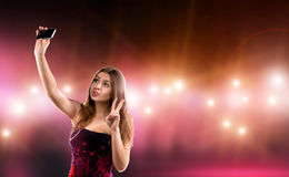 Sexy young woman in dress making selfie, surrounded by care and camera flash. Celebrity, model, star Royalty Free Stock Photography