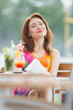 Sexy young woman drinking coctail. Beautiful young lady enjoying her fresh cocktail sitting in a restaurant outdoors Royalty Free Stock Photo