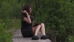 Sexy young woman in elegant black dress using digital tablet while sitting on a wooden pier in summer day. Green grass stock video
