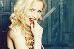Sexy attractive lady. Sexy young woman with emotional pretty smiling face and blonde curly hair with red lips closeup, copy space royalty free stock photo