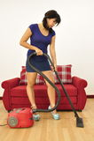 Young woman in outfit vacuums at home Royalty Free Stock Photo