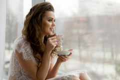 Sexy young woman in erotic transparent underwear drinks coffee on window sill. Cityscape on background Royalty Free Stock Images