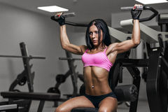 Sexy young woman exercises workout in gym Royalty Free Stock Photography
