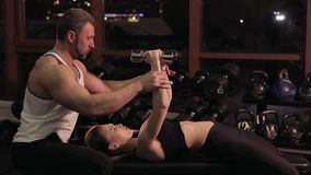 Sexy young woman exercising in gym with fitness instructor stock footage