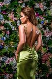 young woman in gorgeous green dress on a flower background. Graceful back and hip lines. Fasion vertical photo stock photography
