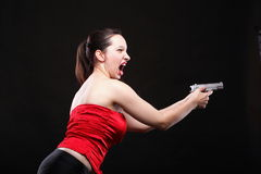 Sexy young woman - gun on black background Stock Images