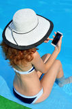 Young woman in a hat with a wide brim with a telephone near. The pool. Bright summer picture girl on vacation with a smartphone in hand royalty free stock image
