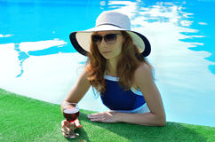 Sexy young woman in a hat with a wine glass, space for text. Royalty Free Stock Image