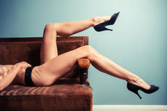 Sexy young woman in heels on a sofa Royalty Free Stock Photography