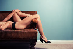 Sexy young woman in heels on a sofa Stock Images