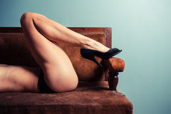 Sexy young woman in heels on a sofa Royalty Free Stock Photos