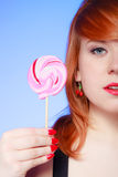 Sexy young woman holding candy. Redhair girl eating sweet lollipop Stock Photo