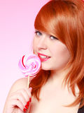 Sexy young woman holding candy. Redhair girl eating sweet lollipop Stock Image