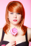 Sexy young woman holding candy. Redhair girl eating sweet lollipop Royalty Free Stock Images