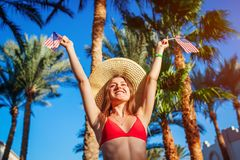 Sexy young woman holding USA flag in under palm trees. Celebrating Independence day of America. Sexy young woman holding USA flag under palm trees. Celebrating stock photo