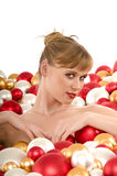 Sexy young woman immersed in Christmas balls Royalty Free Stock Images