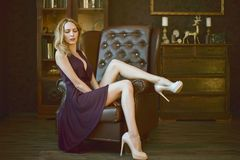 Free Sexy Young Woman In A Purple Dress Sits In A Large Vintage Leather Executive Chair In An Expensive Luxury Dark Interior Stock Image - 150396831