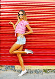 young woman in jeans shorts, shirt and sunglasses posing ou Stock Images
