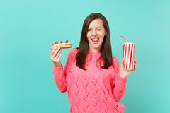 young woman in knitted pink sweater blinking, showing tongue, licking lips hold eclair cake, plastic cup of cola or royalty free stock image