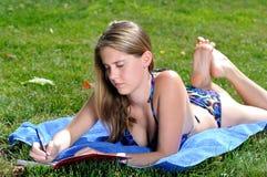 young woman laying out in bikini - writing Stock Image