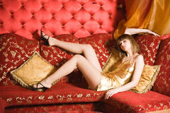 young woman laying on red couch Royalty Free Stock Photos