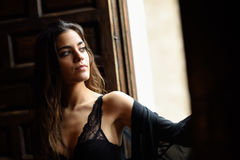 Sexy young woman in lingerie posing near a window Royalty Free Stock Image