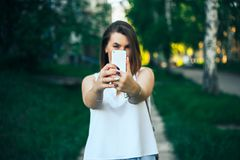 young beautiful woman, teenager, making selfie in park, girl is unfocused, focus on smartphone royalty free stock images