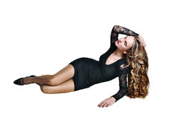 Sexy young woman with long hair in black dress. Lying on white background Royalty Free Stock Photography