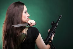 Sexy young woman long hair - gun knife Royalty Free Stock Photo