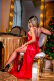 Sexy young woman in a long red dress sits at a festive table over christmas tree lights and candles background. Healthy long hair