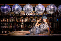 Sexy young woman lying on the bar at a night disco club Stock Images