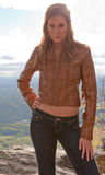 Sexy Young Woman on Mountain. A portrait of an attractive young woman standing on a mountaintop wearing a leather jacket and jeans Royalty Free Stock Photography