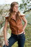 Sexy Young Woman on Mountain. A portrait of an attractive young woman standing on a mountaintop wearing a leather jacket vest and jeans Stock Image