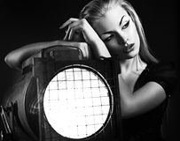 Sexy young woman with old floodlight. Over dark background Stock Photo