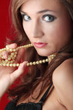 Sexy young woman with a pearls. Sexy young woman with a pearl necklace over red background Stock Images