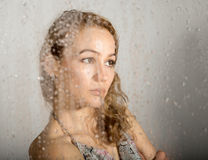 Sexy young woman, posing behind transparent glass covered by water drops. melancholy and sad female portrait Stock Photography