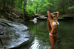 Sexy young woman posing in designer bikini at exotic location of mountain river Stock Photo