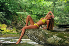 young woman posing in designer bikini at exotic location of mountain river Royalty Free Stock Photography