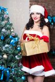 Young woman. Posing with a gift box wearing like Santa`s helper royalty free stock photography