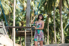 Sexy young woman posing near the swing on the tropical beach, paradise island Bali, Indonesia. Sunny day, happy vacation. Sexy young woman posing near the swing Stock Images