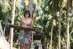 young woman posing near the swing on the tropical beach, paradise island Bali, Indonesia. Sunny day, happy vacation Stock Images