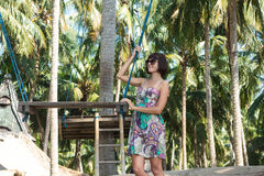 Sexy young woman posing near the swing on the tropical beach, paradise island Bali, Indonesia. Sunny day, happy vacation. Sexy young woman posing near the swing Royalty Free Stock Photos