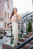 Sexy young woman posing outdoors. On a background of buildings standing on the stairs dressed in a long silver dress royalty free stock image