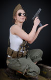Sexy young woman posing in WW2 military uniform and a weapon Stock Image